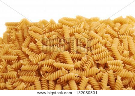 Pile of dry rotini yellow pasta over isolated white background
