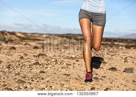 Summer trail running athlete runner legs lower body crop. Fitness woman jogging living an active lifestyle jogging on rocky path in mountain nature landscape. Shoes, knees, thighs weight loss concept.