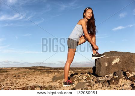 Fitness woman tying running shoes laces getting ready for race marathon in desert summer landscape. Asian trail runner in preparation for cardio workout to get in shape lacing sports footwear.
