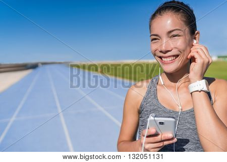 Asian runner woman listening to running motivation music with earbuds on her mobile phone app for run on track and field blue lanes tracks in athletics stadium. Athlete enjoying fitness active life.