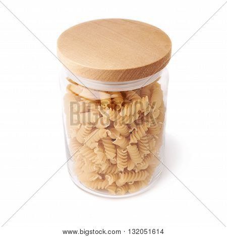 Glass jar filled with dry rotini yellow pasta over isolated white background