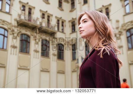 Pensive beautiful young woman walking in the city
