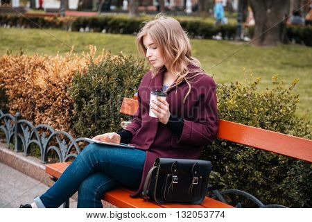 Thoughtful lovely young woman drinking coffee and using tablet on the bench in park