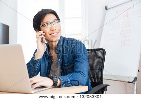 Smiling asian young businessman with laptop talking on mobile phone in office