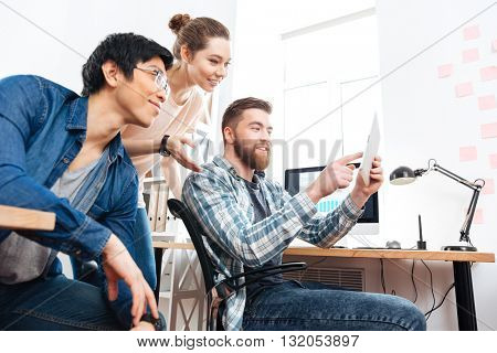 Three happy young businesspeople working and using tablet in office