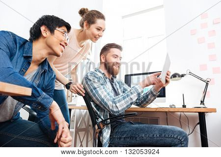 Three smiling young businesspeople working with tablet in office