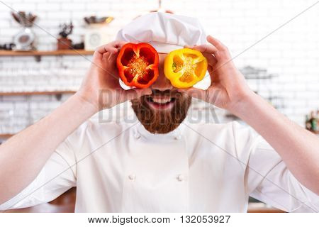 Playful bearded chef cook holding halves of red and yellow bell peppers in front of his eyes and smiling