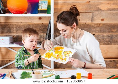 Beautiful young mother teaching her little son painting in art school