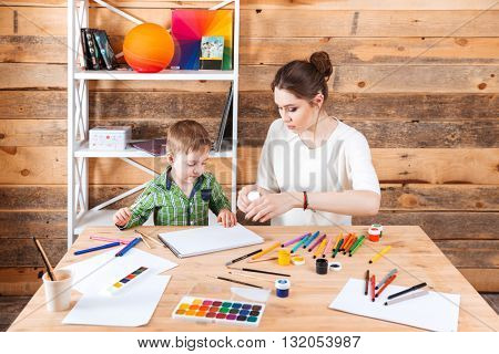 Concentrated mother and little son sitting and drawing in art school