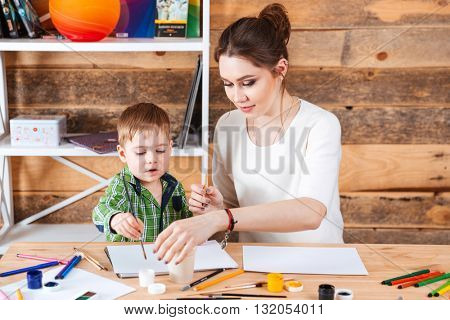 Beautiful mother and her little son sitting and painting in art school