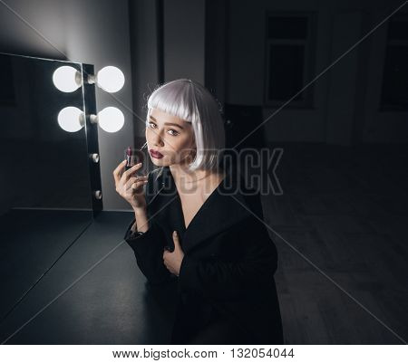 Tender attractive young woman in blonde wig applying lipstick near the mirror in dressing room