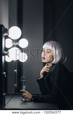 Pensive pretty young woman with glass of champagne sitting and thinking in dressing room