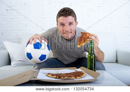 young man watching football game on television sitting on sofa couch with soccer ball at home eating pizza and holding beer bottle looking excited and anxious