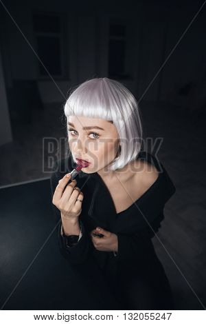 Portrait of attractive young woman in blonde wig sitting and applying lipstick in dark dressing room