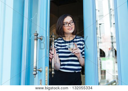 Happy lovely young woman standing and looking out of cafe with blue door
