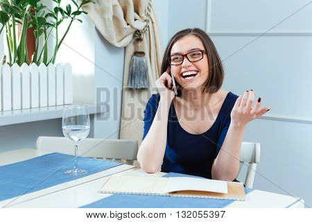 Cheerful charming young woman in glasses talking on mobile phone and laughing in cafe
