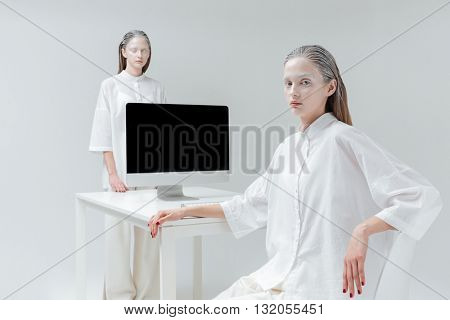 Two fashion beautiful girls sitting and standing near the desk with computer, pc over gray background