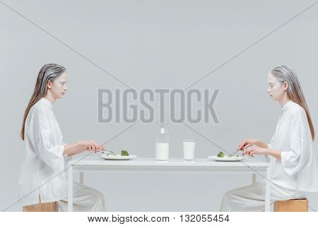 Two beautiful fashion women having lunch at the table over gray background