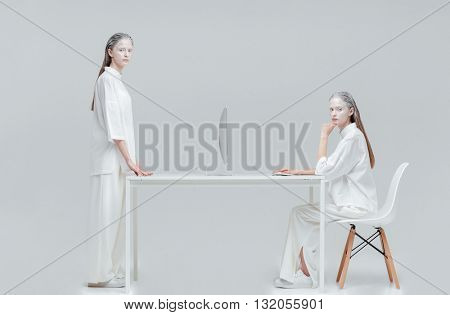 Two cosmic mystical women using future technology, computer over gray background