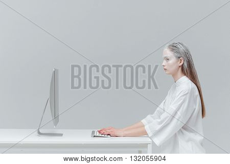 Woman sitting at the table with computer, pc over gray background