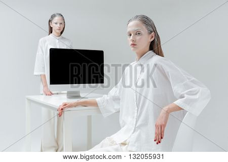 Two fashion mystical beautiful woman sitting beside table with computer, pc over gray background