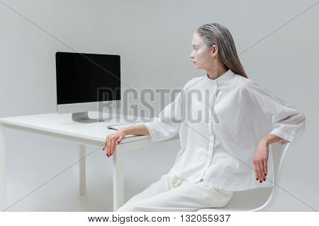 Pretty mysterious girl looking at the computer screen over gray background