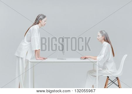 Two beautiful women using future technology, computer and looking at each other over gray background