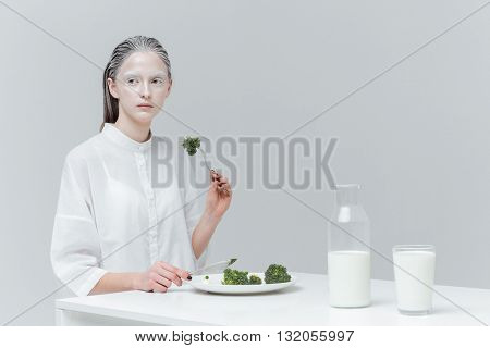 Beautiful falien, fashion woman having meal at the table over gray background