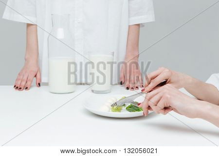 Close-up of hands holding knife and fork over vegetable salad during lunch over gray background