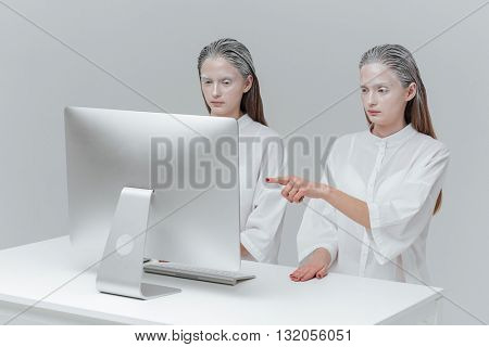 Two cosmic fashion women sitting at the computer. Girl pointing finger at the screen over gray background
