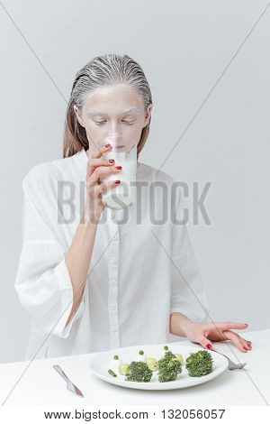 Beautiful fashion girl drinking milk and having lunch at the table over gray background