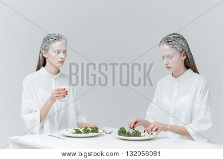 Two beautiful pretty fashion girls eating at the table over gray background