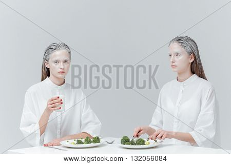 Two beautiful young girls having meal at the table over gray background