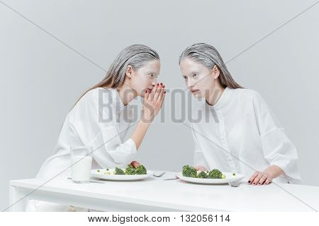 Two beautiful fashion girls talking and eating at the table over gray background