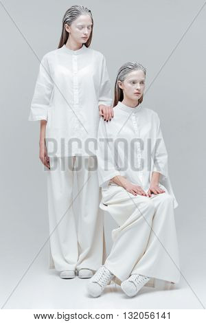 Two women in white fashion clothes over gray background