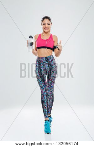 Full length portrait of a happy sports woman holding shaker with water and showing thumb up isolated on a white background