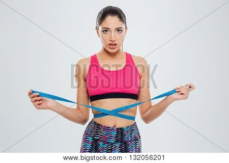 Unhappy sports woman measuring waist with tape isolated on a white background