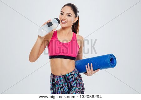 Happy woman holding yoga mat and drinking water isolated on a white background