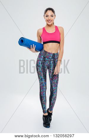 Full length portrait of a happy woman holding yoga mat isolated on a white background