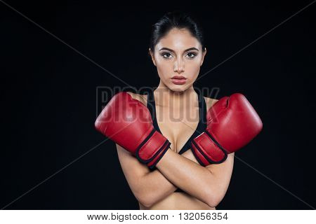 Female boxer showing stop gesture with hands on black background