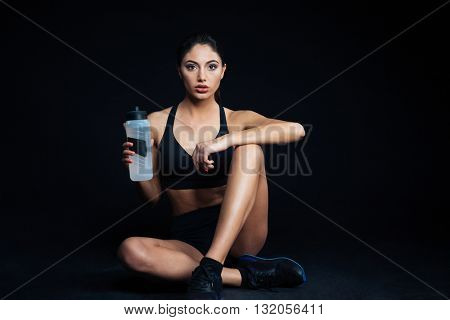 Fitness woman sitting on the floor with bottle of water on black background