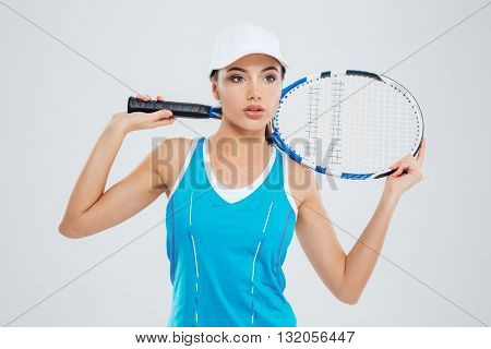 Pensive sports woman standing with tennis racquet isolated on a white background