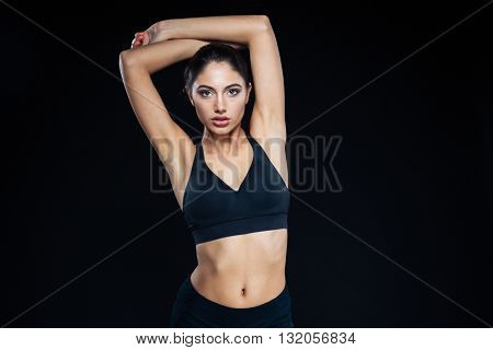 Portrait of a cute fitness woman posing on black background