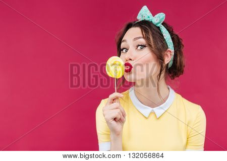 Happy pretty pinup girl eating and kissing yellow lollipop over pink background