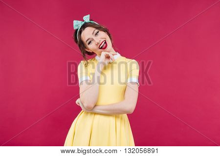 Cheerful beautiful pinup girl in yellow dress standing and smiling over pink background
