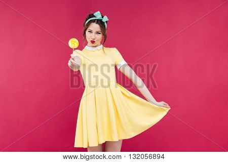 Smiling attractive pinup girl in yellow dress showing sweet lollipop over pink background