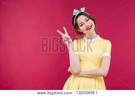 Smiling charming young woman in yellow dress showing peace sign over pink background