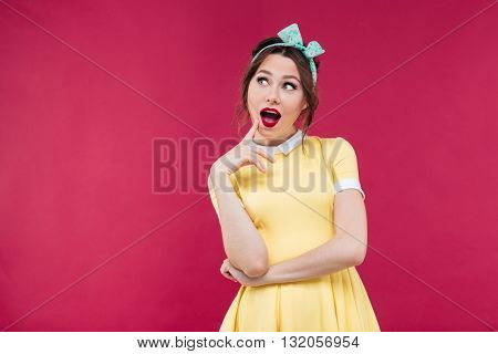 Smiling pensive pinup girl in yellow dress thinking over pink background