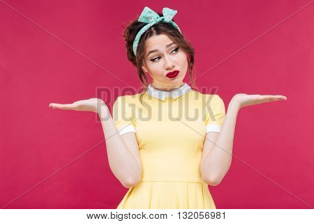 Upset lovely pinup girl holding copyspace on both palms over pink background