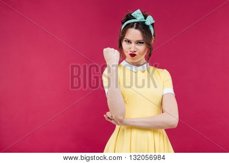 Angry pretty pinup girl in yellow dress showing her fist over pink background